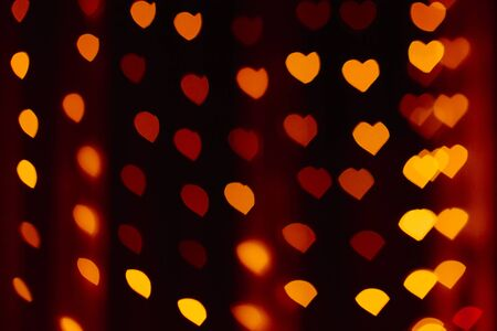 Red, yellow and orange highlights or bokeh in the form of hearts, traces of lights out of focus. Festive background for Valentines day Фото со стока