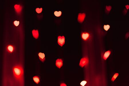 Red and pink highlights or bokeh in the form of hearts, traces of lights out of focus. Festive background for Valentines day