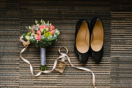Accessories for the bride on the wedding day: shoes, a beautiful bouquet, a bottle of toilet water and a satin ribbon on a striped background Фото со стока