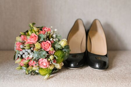 Accessories for the bride on the wedding day: shoes, a beautiful bouquet on a beige background Фото со стока