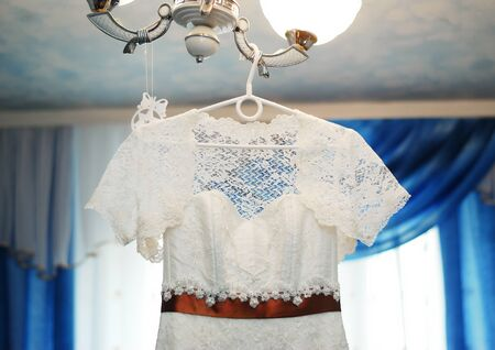A white wedding dress with a brown satin ribbon at the waist hangs on a chandelier in the living room. Clothing for the bride Stok Fotoğraf
