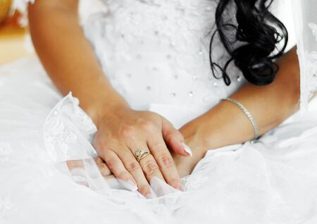 The brides hands with a French manicure are on her lap.