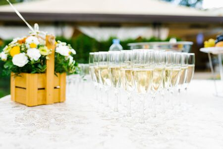 Many glasses of champagne on the buffet table and a basket of fresh flowers.