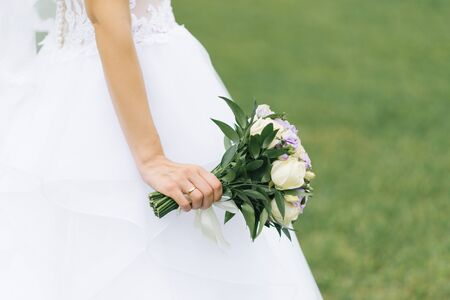 Beautiful delicate wedding bouquet of the bride with lilac eustoma and cream roses in the hands of the bride. Stockfoto
