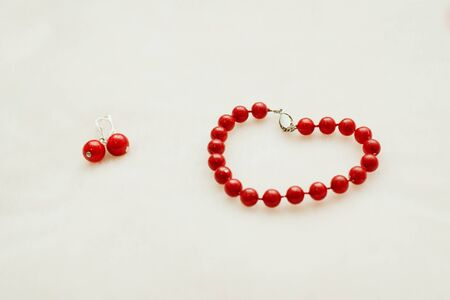 Red jewelry: bracelet and earrings with beads on a white background.