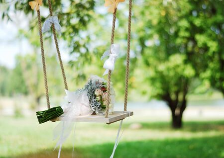 Stylish beautiful delicate wedding bouquet of the bride lies on the garden swing in the summer.