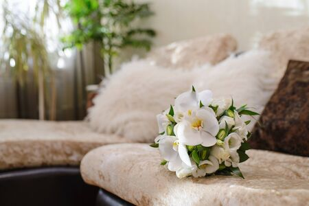 A delicate and beautiful Bridal bouquet of white orchids and red roses lying on the sofa in the room.