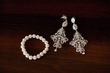 Jewelry for the bride: patterned earrings and bracelet on a dark brown background. Selective focus.