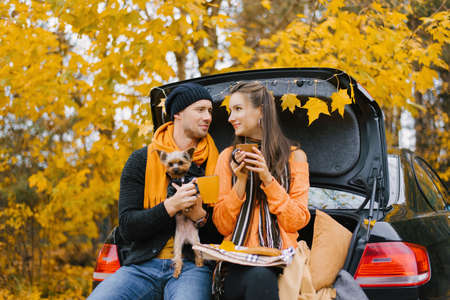 A happy young family is relaxing after a day spent outdoors in the autumn forest. A couple in love is sitting in the trunk of a car and drinking tea from a thermos with their dog. Travel in the autumn season.