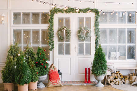 Porch with a white door in Christmas decorations and Christmas trees. Spruce garlands around the door. Beautiful winter terrace of the house with garlands of retro light bulbs