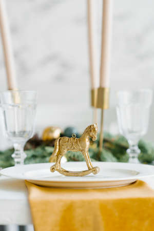 Gold figurine of a vintage horse in the design of a festive serving of a Christmas dinner or lunch