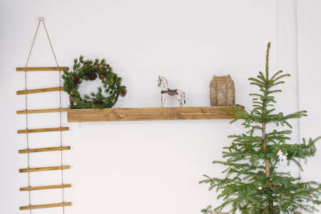 Christmas decor in the interior of the house: a wooden shelf on which stands a toy horse and a wreath of fir branches. Christmas tree without toys