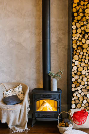 Retro fireplace, wood and armchair with a blanket and pillows in a country house