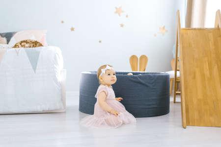 Little girl 1 year old sits on the floor in the children's room Reklamní fotografie