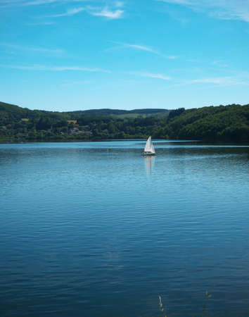 Photo of a lake in the south of France, where a sailboat is sailing