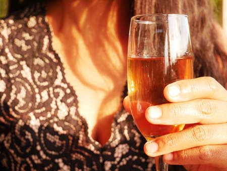 Close-up of the cleavage of a woman holding a glass of wine Standard-Bild
