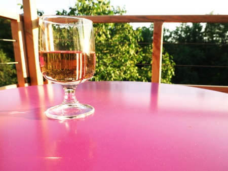 Glass of wine on a pink table with nature in the background