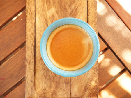 Close-up of a coffee cup seen from above on a wooden table Summer color during a meal with friends in the south of France Stock Photo