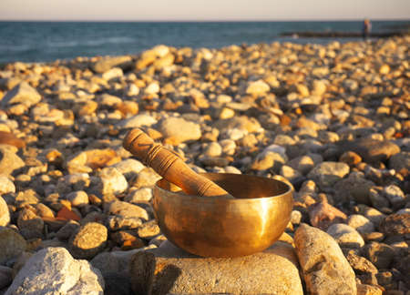 Singing bowl on pebbles with the sea in the background 版權商用圖片