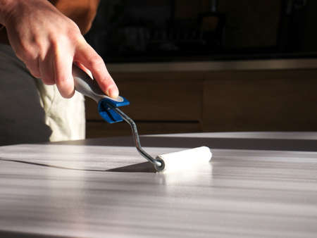 Close-up on the hand of a man doing DIY, painting a piece of furniture with a brush