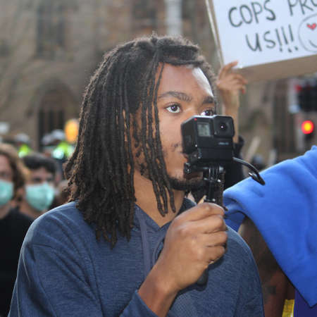Young man with dreadlocks holding a point and shoot video camera, recoding as he marches with the protest crowd. Black Lives Matter Protest March. Protesting Aboriginal deaths in custody and the death of George Floyd. During a worldwide pandemicofcoro