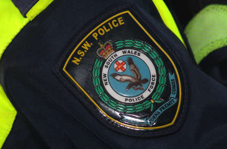 Close up of the badge on a NSW police officers hi vis jacket. Black Lives Matter Protest March. Protesting Aboriginal deaths in custody and the death of George Floyd. During a worldwide pandemicofcoronavirus disease 2019 (Covid 19) Sydney, NSW / Austr