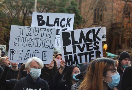 A protest crowd marching with signs. Some of the signs read 'truth justice peace' and 'black lives matter'. Black Lives Matter Protest March. Protesting Aboriginal deaths in custody and the death of George Floyd. During a worldwide pandemicofcoronavir