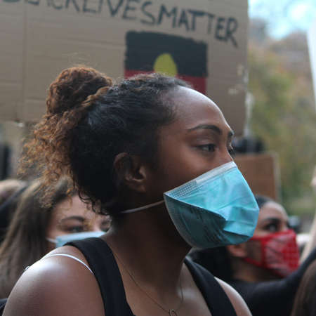 Young woman with a face mask and her hair in a bun marching with the protest crowd. Black Lives Matter Protest March. Protesting Aboriginal deaths in custody and the death of George Floyd. During a worldwide pandemicofcoronavirus disease 2019 (Covid 1 Redakční