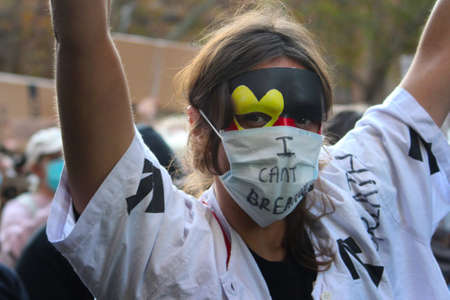 A young woman wearing prisoner clothing, a mask in aboriginal colours and a surgical a mask that reads 'I cant breathe'. She is holding up a sign while she marches with the crowd. Black Lives Matter Protest March. Protesting Aboriginal deaths in custody a