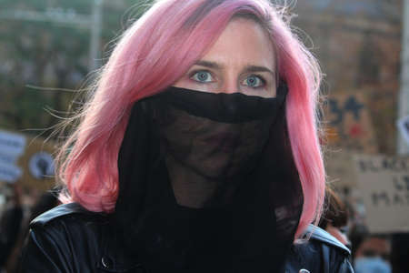 A young woman with pink hair and a veil over her face marching with the protest crowd. Black Lives Matter Protest March. Protesting Aboriginal deaths in custody and the death of George Floyd. During a worldwide pandemicofcoronavirus disease 2019 (Covi Redakční
