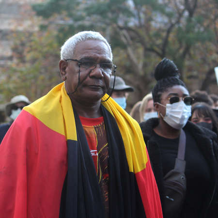 A man with grey hair wearing and Aboriginal flag over his shoulders. Black Lives Matter Protest March. Protesting Aboriginal deaths in custody and the death of George Floyd. During a worldwide pandemicofcoronavirus disease 2019 (Covid 19) Sydney, NSW  Reklamní fotografie - 151081891