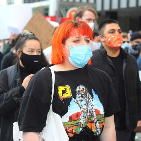 Woman with orange hair and a face mask marching with the crowd. Black Lives Matter Protest March. Protesting Aboriginal deaths in custody and the death of George Floyd. During a worldwide pandemicofcoronavirus disease 2019 (Covid 19) Sydney, NSW / Aus
