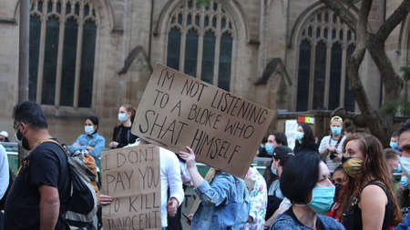 Protestors in the crowd holding signs reading 'I don't pay you to kill innocent' and 'Im not listening to a bloke who shat himself'.  Black Lives Matter Protest March. Protesting Aboriginal deaths in custody and the death of George Floyd. During a worldwi Redakční