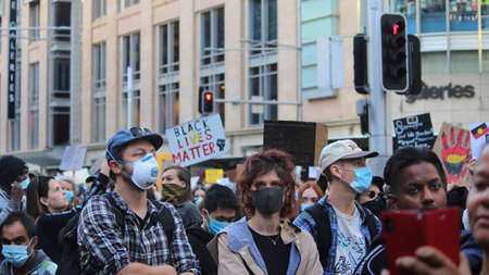 Group of protestors marching with face masks on. Black Lives Matter Protest March. Protesting Aboriginal deaths in custody and the death of George Floyd. During a worldwide pandemicofcoronavirus disease 2019 (Covid 19) Sydney, NSW / Australia - June 6