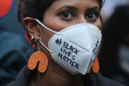 Woman wearing a face mask reading '# black lives matter'. she also has on large orange earrings. Black Lives Matter Protest March. Protesting Aboriginal deaths in custody and the death of George Floyd. During a worldwide pandemicofcoronavirus disease