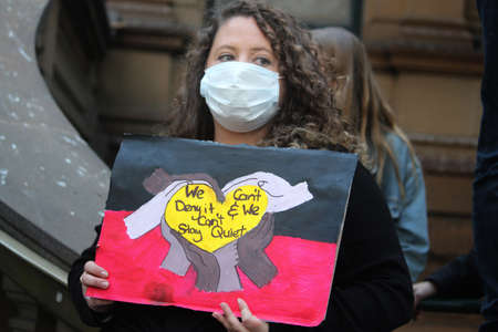 Young woman holding a sign reading 'we cant deny it and cant stay quiet'. Black Lives Matter Protest March. Protesting Aboriginal deaths in custody and the death of George Floyd. During a worldwide pandemicofcoronavirus disease 2019 (Covid 19) Sydney, Redakční