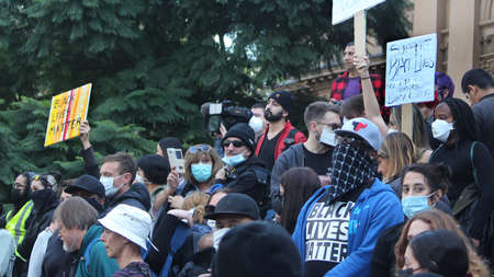 Crowd gathered on Town Hall steps to watch the rally. Some people are wearing face masks. Black Lives Matter Protest March. Protesting Aboriginal deaths in custody and the death of George Floyd. During a worldwide pandemicofcoronavirus disease 2019 (C