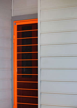 Bright orange screen security door on a weather board house. Inner west, Sydney