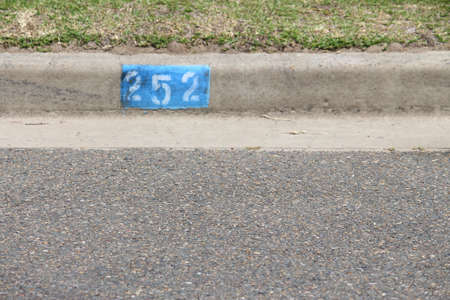 House number stencil painted onto the kerb of a bitumen road. Kurnell, Sydney