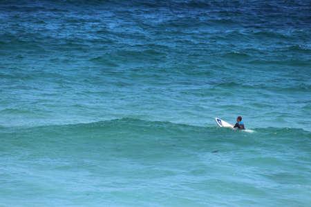 Lone surfer waiting for a wave in a big ocean. Tamarama Beach, Sydney