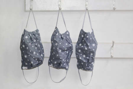 Just washed and hung to dry. Three grey fabric with star pattern face masks hanging on wall hooks.