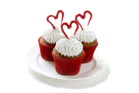 Cupcakes for Valentines day. Chocolate cupcakes with vanilla frosting. Hearts made of red colored white chocolate.                   photo