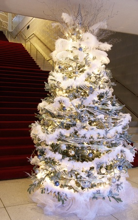 Christmas tree decorated with in silver, blue, and white