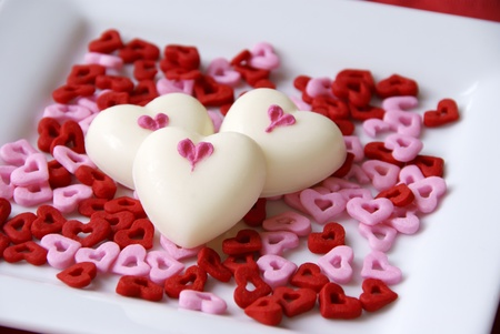 White chocolate hearts on a bed of heart sprinkles