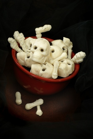 White chocolate skulls and body parts in a red bowl.