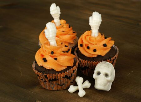 Chocolate cupcakes decorated with white chocolate skeleton parts.