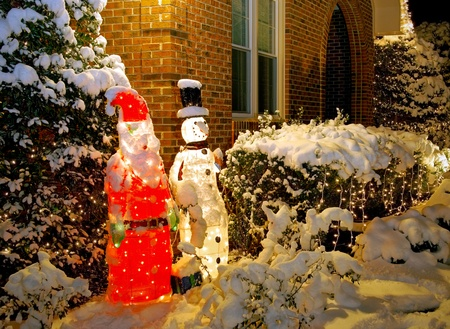 Outdoor Santa and Snowman decorations covered in snow