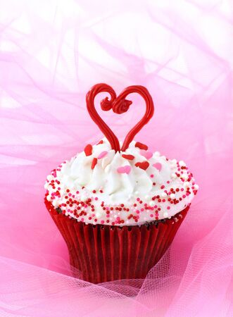 Cupcake decorated with sprinkles and a red chocolate heart                 Stock Photo