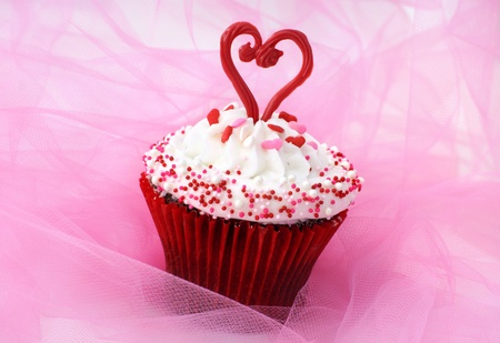 Cupcake decorated with sprinkles and a red chocolate heart Imagens - 11835801