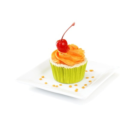 Vanilla cupcake with vanilla frosting topped with a maraschino cherry, on white background